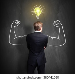 successful businessman standing in front of a blackboard with a drawn lightbulb, symbolizing having an idea