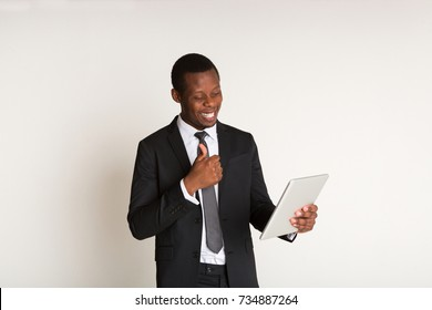 Successful businessman in stylish suit, tie standing, looking at tablet. Portrait. Copy space, white background