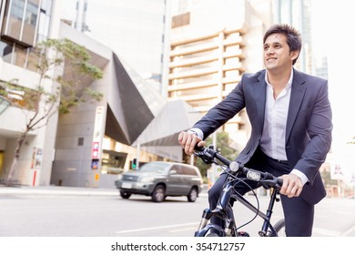 Successful businessman in suit riding bicycle