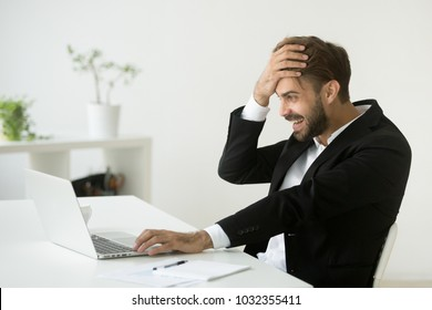 Successful businessman in suit shocked by unbelievable online offer or internet win looking at laptop screen, amazed entrepreneur excited with business result, profit growth, achievement or good news