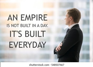 """Successful businessman in suit standing in office with hands crossed on chest, looking through window at big city. Photo with motivational text """"An empire is not built in a day. It is built everyday"""""""