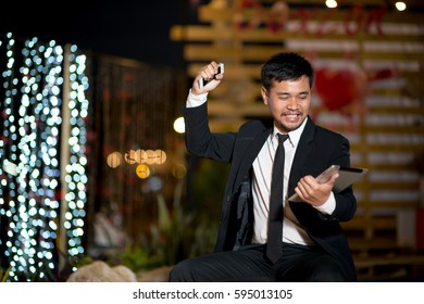 successful businessman in suit using modern smart phone at night city in the blurred background with bokeh light, male hands holding tablet and phone