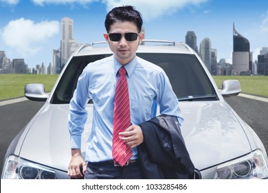 Successful businessman with sunglasses in front of luxurious car