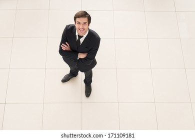 Successful businessman. Top view of cheerful young man in formalwear keeping arms crossed and smiling at camera