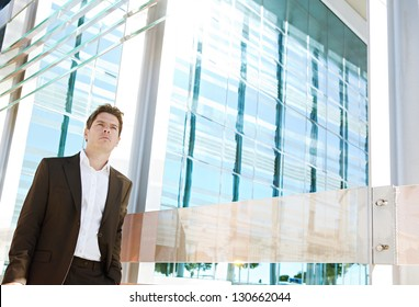 Successful businessman walking by a modern glass office building in the financial district city on a sunny day, outdoors.
