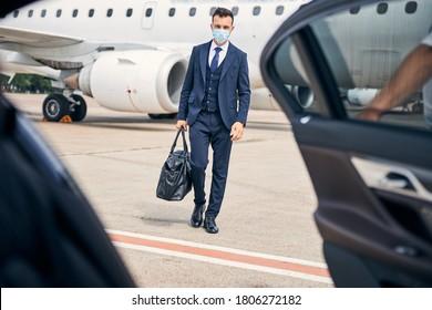 Successful businessman wearing a facial mask walking towards a car