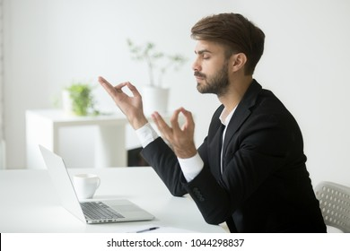 Successful businessman wearing suit meditating in office for concentration development, calm mindful ceo practicing yoga at workplace focused on relaxation after hard work sitting in front of laptop