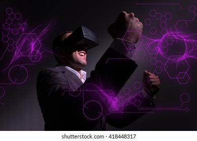 successful businessman wearing virtual reality glasses and celebrating a victory. Futuristic overlay design