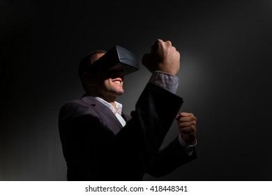 successful businessman wearing virtual reality glasses and celebrating a victory