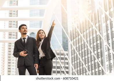 successful businessman and women pointing his finger to sky. Business success concept