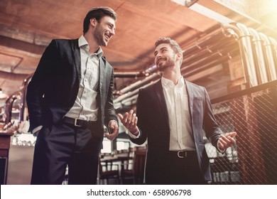 Successful businessmen are communicating in bar and smiling. Discussing the latest news.