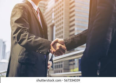 Successful businessmen handshaking after negotiation on city background.