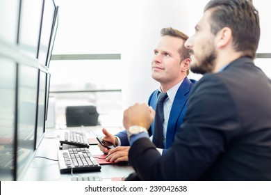 Successful businessmen trading stocks. Stock traders looking at graphs, indexes and numbers on multiple computer screens. Colleagues in traders office. Business success.