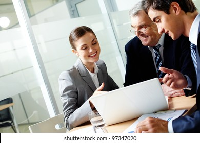 Successful businessteam of three sitting in office and planning work