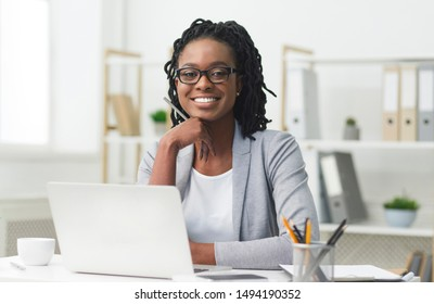 Successful Businesswoman. Afro Girl Sitting At Laptop And Smiling In Modern Office. Empty Space For Text