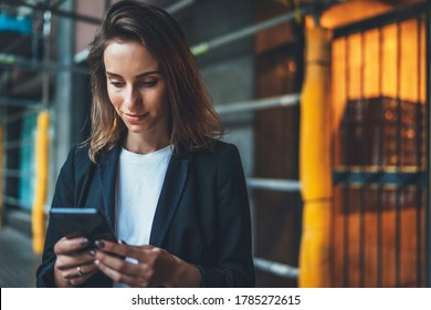 successful businesswoman checks email on smartphone during a lunch break outside office, manager uses mobile phone in city outdoors, women in suit writes  message on cellphone