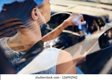 successful businesswoman driving car through modern urban city with reflections of buildings