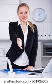 Successful businesswoman standing in office with open hand ready for handshake