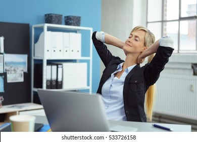 Successful businesswoman taking a moment to de-stress leaning back in her chair with her hands behind her head, closed eyes and a serene smile