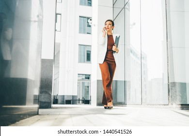 Successful businesswoman talking on phone while walking outdoor. Reflecting in modern white bilding.