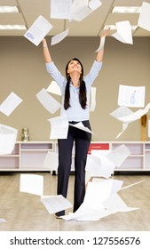 Successful businesswoman throwing papers in the air