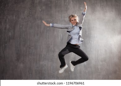 Successful businesswoman. Young blonde woman in business suit and sneakers jumping for joy, gray textured background