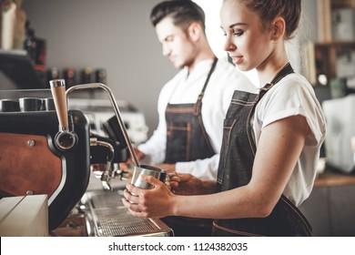 Successful cafe business, professional baristas team using coffee machine