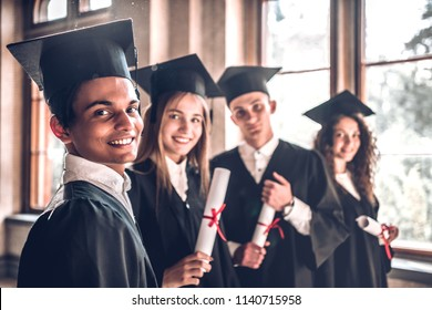 Successful careers - here we come!Group of smiling college graduates standing together in university and smiling looking at camera.