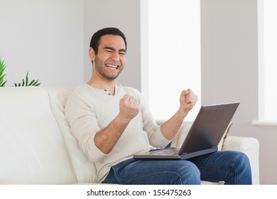 Successful casual man cheering while sitting in bright living room