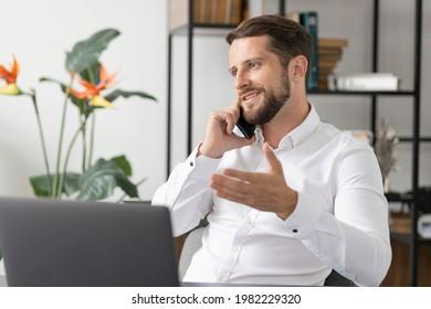 Erfolgreicher vorsichtiger Geschäftsmann, der mit jemandem über Smartphone spricht, während er im Büro mit Laptop arbeitet. Geschäftsführender junger Geschäftsmann, der am Arbeitsplatz telefoniert