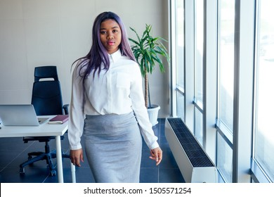 successful charming african american woman with purple hair in white shirt and gray pencil skirt posing in a modern office with a panoramic window