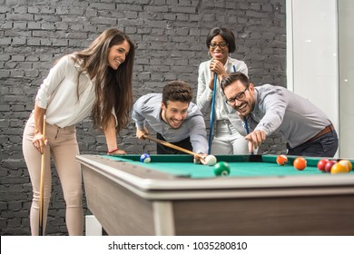 Successful cheerful business people playing snooker.