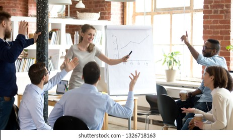 Successful cheerful businesswoman company head presenting new project to multi-ethnic young employees, diverse people voting raising hands or business coach giving presentation to clients in boardroom