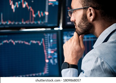 Successful and concentrated trader in formalwear looking at monitor, analyzing global bitcoin price on network diagram, working in office