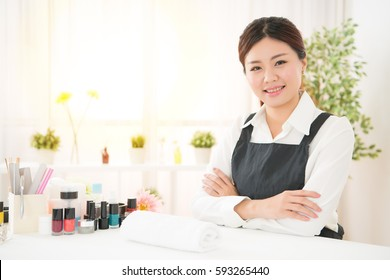 successful confidence gorgeous female asian salon business owner sitting in front of camera ready to showing her manicure professional