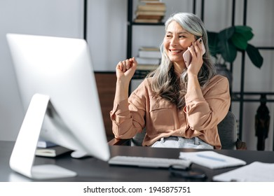 Successful confident beautiful senior gray-haired asian woman, business leader, manager, working at the office, talking on the phone with friends or colleagues, looking away, smiling