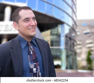 A successful, confident business man is standing in front of a downtown building and looking off into the future. Add your text message to the side.