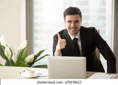 Successful confident businessman looking at camera, showing thumbs up or like sitting at office desk, effective solutions, recommending best choice for business, sign of success, good idea, great job