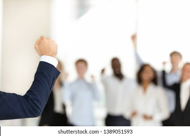 Successful confident businessman make speech show clenched fist demonstrate power and strength, excited diverse work team businesspeople support male leader together. Unity, leadership concept