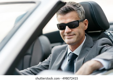 Successful confident businessman sitting in his brand new convertible car, he is smiling at camera