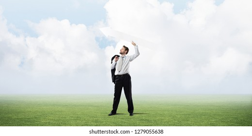 Successful and confident businessman in suit starting launching huge white arrow to the air while standing on green lawn and cloudy skyscape view on background