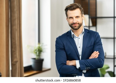 Successful confident young bearded brunet adult male entrepreneur businessman professional in business casual clothes standing with arms crossed folded at the modern home office and looking at camera - Shutterstock ID 1926860858
