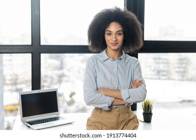 Successful confident young mixed-race female entrepreneur or a businesswoman with Afro hairstyle in casual clothes standing with arms folded in the office with the panoramic view, looking at camera