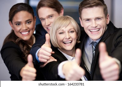 Successful corporate team showing thumbs up