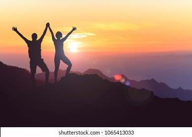Successful couple achievement climbing or hiking, business concept with man and woman celebrating with arms up raised, outstretched outdoors. Motivational and inspirational silhouette landscape.
