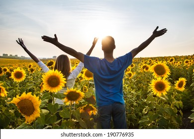 Successful couple of young raising arms to summer sunset sky