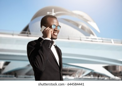 Successful dark-skinned businessman wearing elegant black suit and round sunglasses having pleased smile while speaking over smart phone with his business partner isolated over big city background