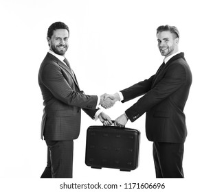 Successful deal concept. Handover of suitcase in hands of partners on white background. Businessmen with happy faces shaking hands and hold briefcase. Business exchange between businessmen in suits.