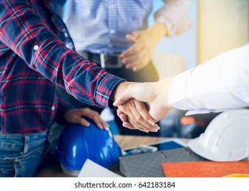 Successful deal, Female architect shaking hands with client in construction site after confirm blueprint for renovate building.