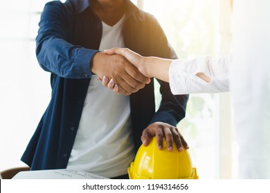 Successful deal, male architect shaking hands with client in construction site after confirm blueprint for renovate building.